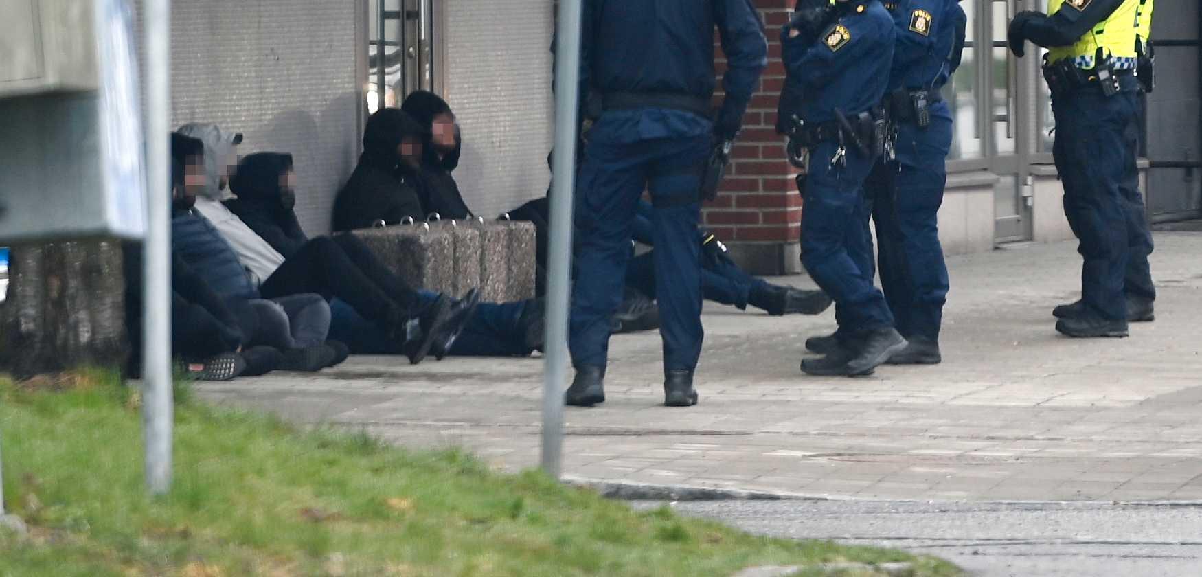 Flera personer sattes mot en husfasad i samband med insatsen vid Attunda tingsrätt i Sollentuna.