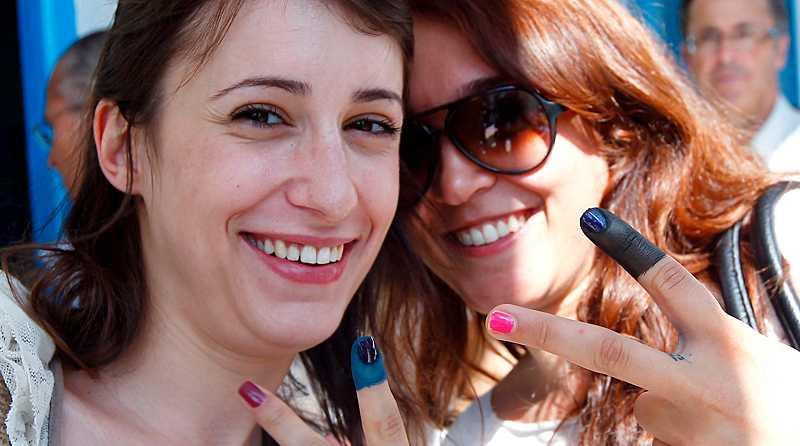 glada väljare Två kvinnor håller upp sina färgade fingrar mot fotografen just efter att de lagt sina röster i det första riktiga valet någonsin i Tunisien i går.