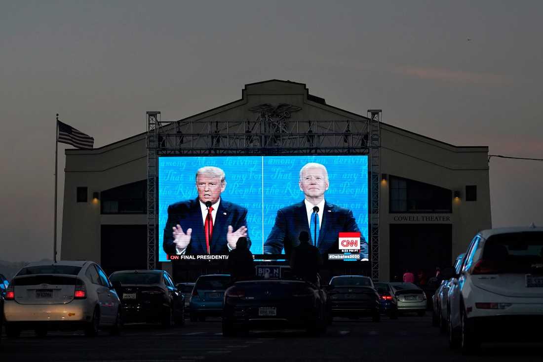 Personer i bilar kollar på presidentdebatten på storskärm.