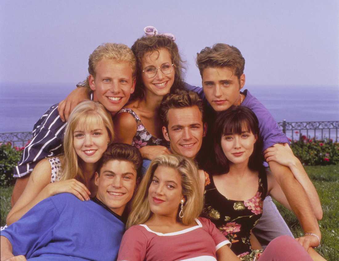 Gabrielle Carteris (som Andrea Zuckerman), Jason Priestly (som Brandon Walsh), Shannen Doherty (som Brenda Walsh), Luke Perry (som Dylan McKay), Tori Spelling (som Donna Martin), Brian Austin Green (som David Silver), Jennie Garth (som Kelly Taylor), Ian Ziering (som Steve Sanders) i Beverly Hills 90210 (FOX) 1990–1994.