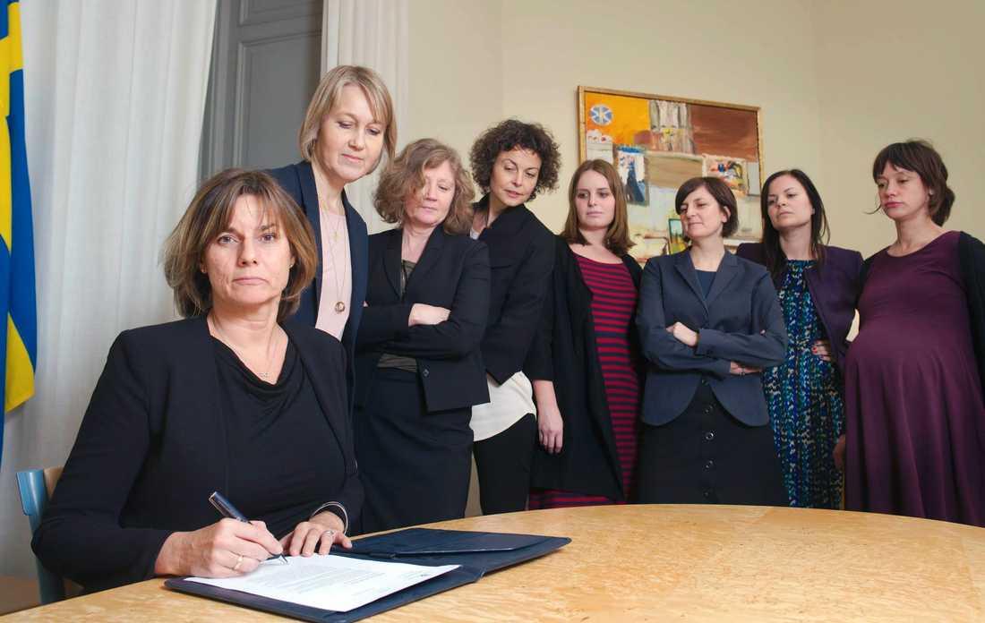 Isabella Lövin (MP) skriver på ny klimatlag omgiven av sju kvinnor.