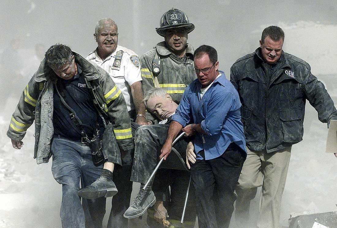 PASTORN DOG Här bärs pastor Mychal Judge bort av brandmän och frivilliga. Han var den första döde som identifierades efter terrordåden. Pastorn gav sista smörjelsen till döda människor innan han själv föll offer för rasmassorna.