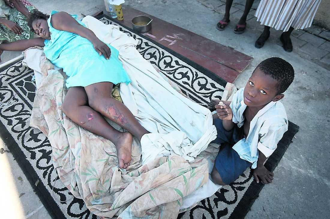 """MAMMA ÄR SKADAD Pierre Fidel, 9, satt och tittade på tecknad film när skalvet kom. Hans syster och pappa saknas. Mamma lever, men hon vrider sig i plågor medan det rinner från de stora, öppna såren på hennes ben. """"Jag vill att hon får komma till sjukhus"""", säger Pierre."""