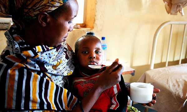 En kvinna i Tanzania med sin malariasjuka dotter på ett sjukhus som bedrivs med hjälp av svenskt bistånd. Det är lätt att plocka pengar från världens fattiga, skriver debattören.