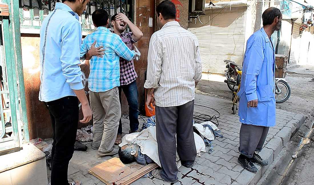 BILDEN AV SORG En ung man skriker ut sin sorg vid sjukhusets ingång. Han har hittat sin döda pappa under en filt på en kartong.