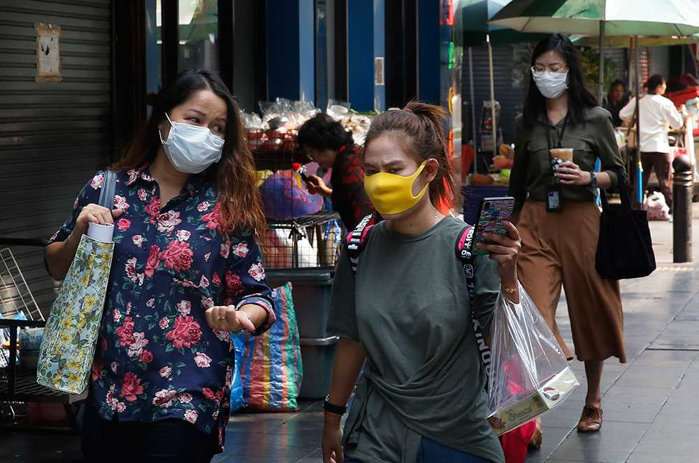 Invånare och turister bär munskydd utomhus.