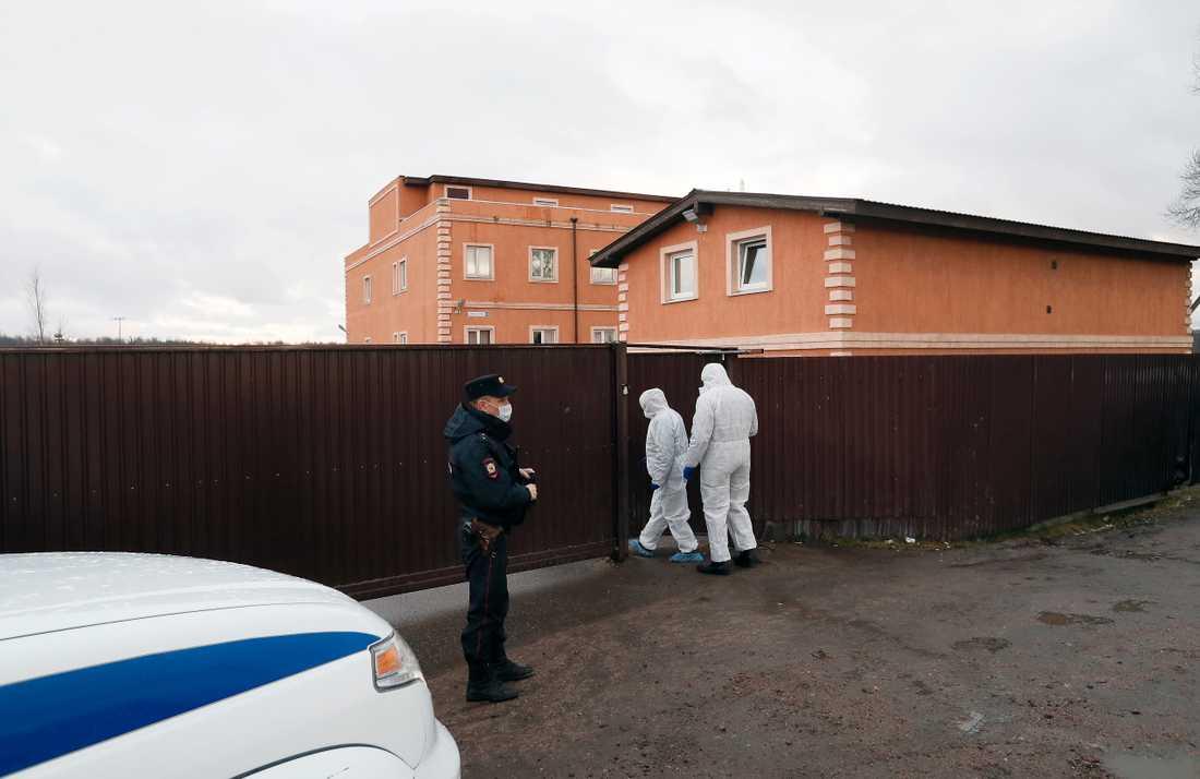 Medicinsk personal i skyddsdräkter går in i boendet för de sjuka Ikea-byggarna i Leningradregionen i Ryssland.