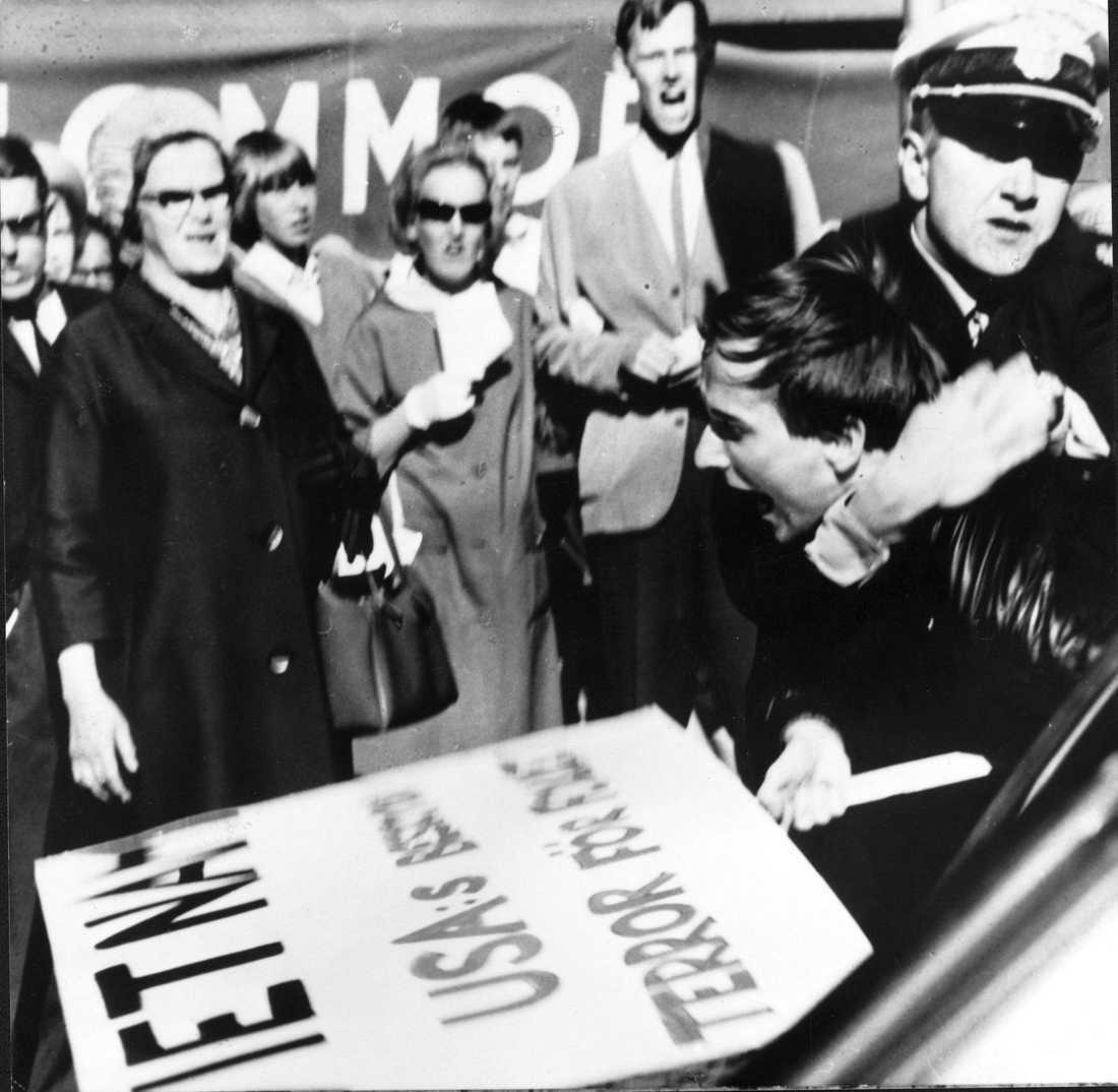 Polisen griper Sköld Peter Matthis under den första svenska  Vietnamdemonstrationen, på Hötorget i Stockholm 1965.