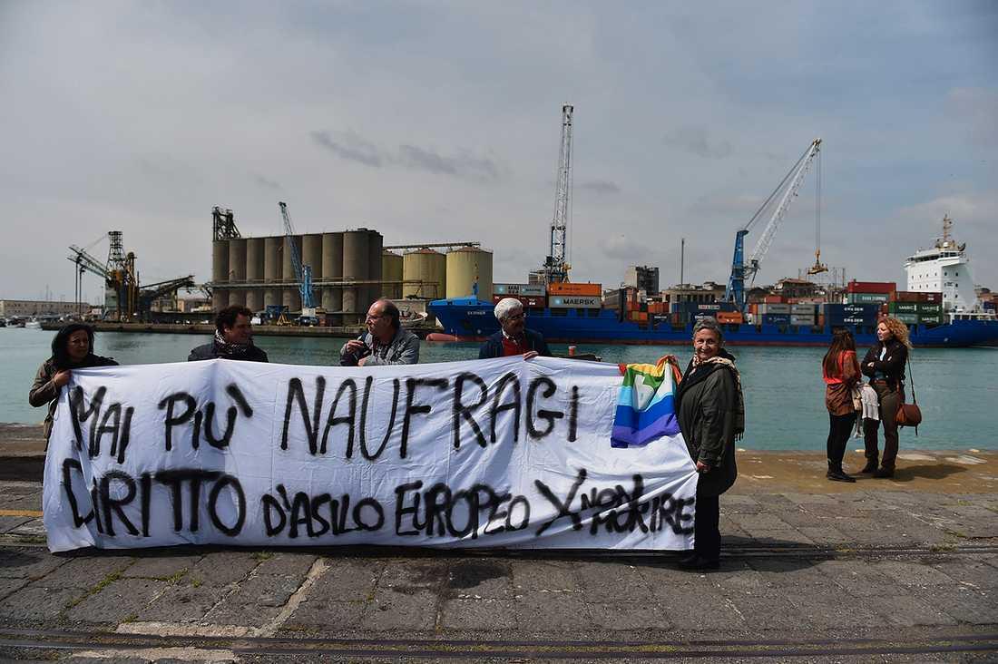 """Demonstranter i hamnen håller en banderoll med texten """"Inga fler skeppsbrott, europeiska rättigheter till asyl för att undvika framtida dödsfall""""."""