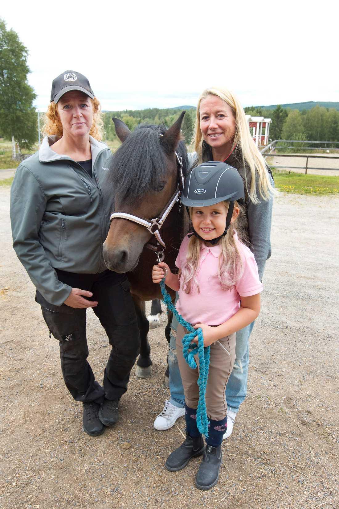 Både mamma Katharina Olsson (till höger) och ridläraren Bettan Lindborg (till vänster) ser hur mycket Storm betyder för Stinas utveckling.
