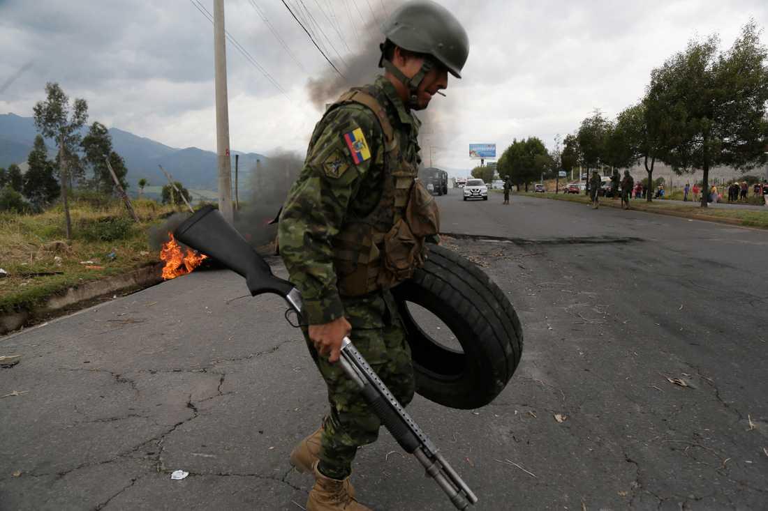 En soldat i Tambillo i Ecuador rensar motorvägen från bråte som lagts dit i samband med protesterna. Bilden är från i lördags.
