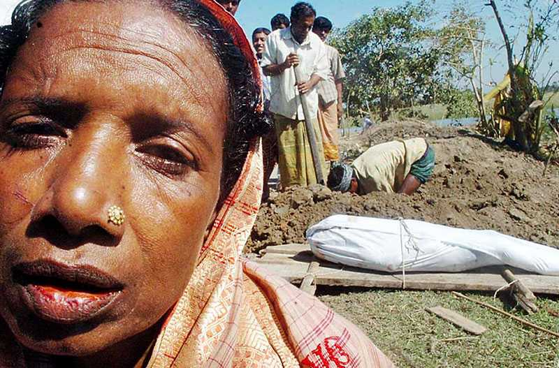 Sörjer en anhörig En kvinna sitter vid kroppen till en anhörig. Lokala hjälparbetare gräver massgravar i byn Nisanbari i Borguna-distriktet i Bangladesh.