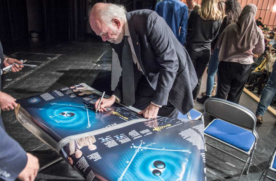 Förra årets fysikpristagare Barry Barish signerar en affisch där hans upptäckt presenteras. Arkivbild.