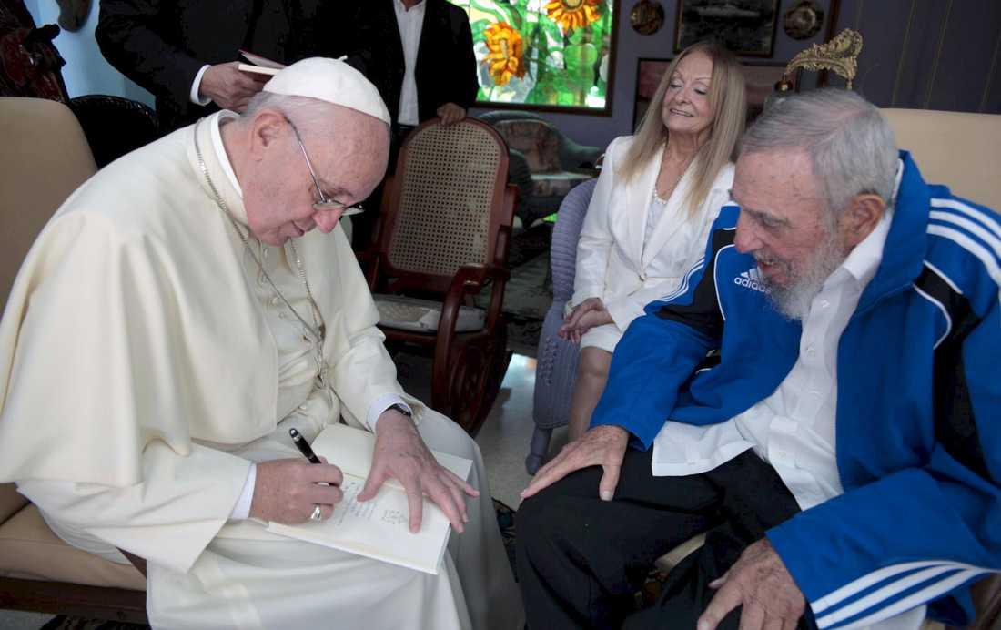 Påve Franciskus skriver i en bok under ett möte med Fidel Castro och hans hustru Dalia Soto del Valle i Havanna, september 2015.