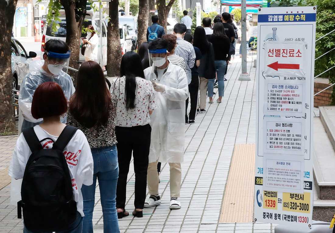 Människor som misstänker att de har smittats av coronaviruset väntar för att testas i Seoulförorten Bucheon på torsdagen.