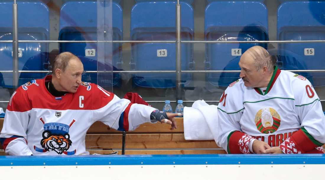 Belarus president Aleksandr Lukasjenko (till höger i bild) intill Rysslands president Vladimir Putin i en ishockeyrink i ryska Sotji i fjol. Arkivbild.