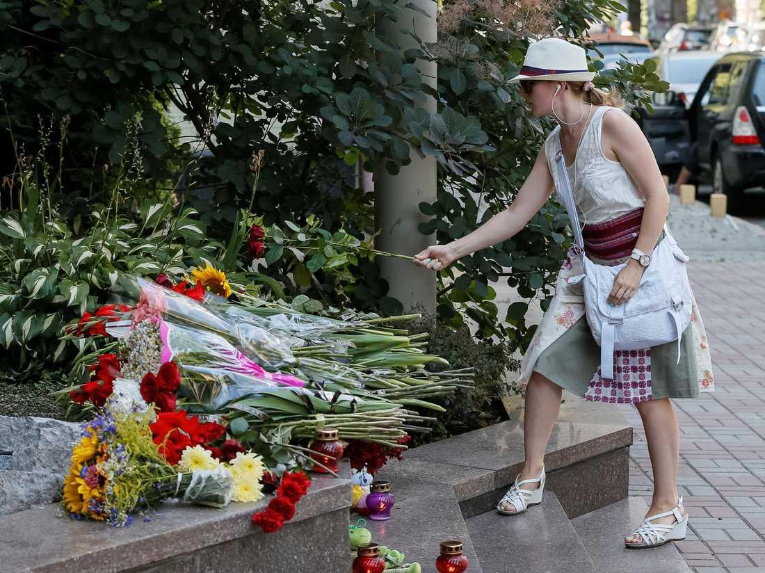 En kvinna lägger ut en blomma för att hedra offren i attacken på Promenade des Anglais.