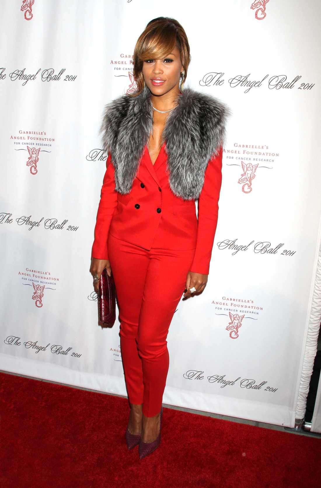 Rapparen Eve, 33, känner att det lackar mot jul och klär sig i rött från topp till tå. På hennes axlar får en pälskrage vila.