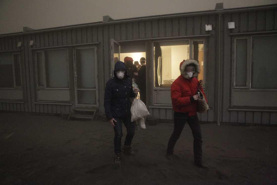 Turister lämnar ett hotell i Nupur, efter att askan fortsätter att välla ut från vulkanen.