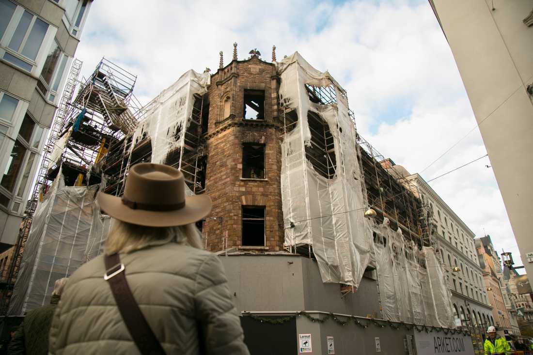Kvinna betraktar ruinen efter branden.
