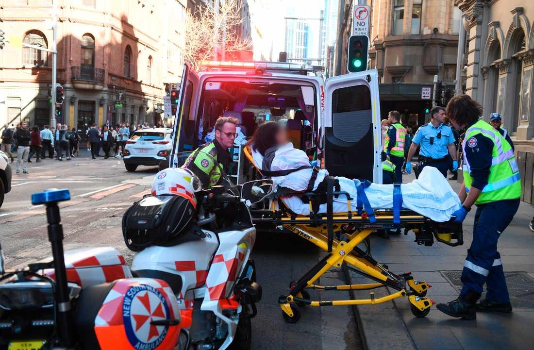 En skadad kvinna tas omhand av ambulanspersonal efter att ha knivhuggits i Sydney.