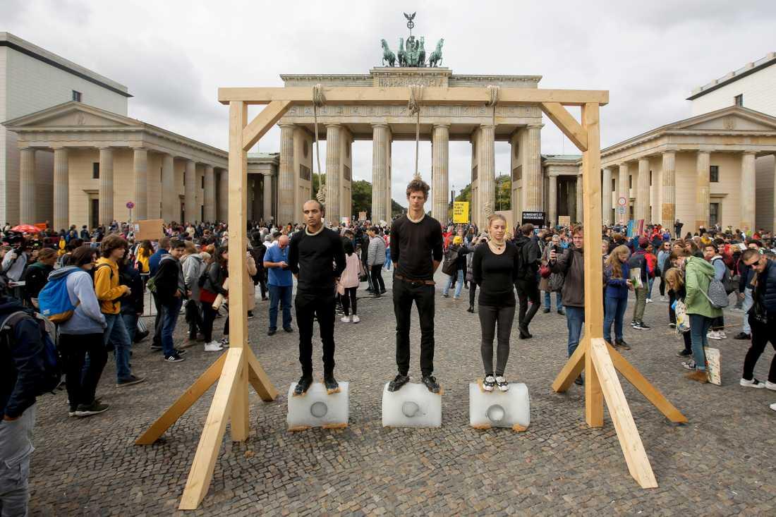 Tre personer i Berlin står på isblock under galgar med hängsnaror runt sina halsar som en protest mot den förda klimatpolitiken.