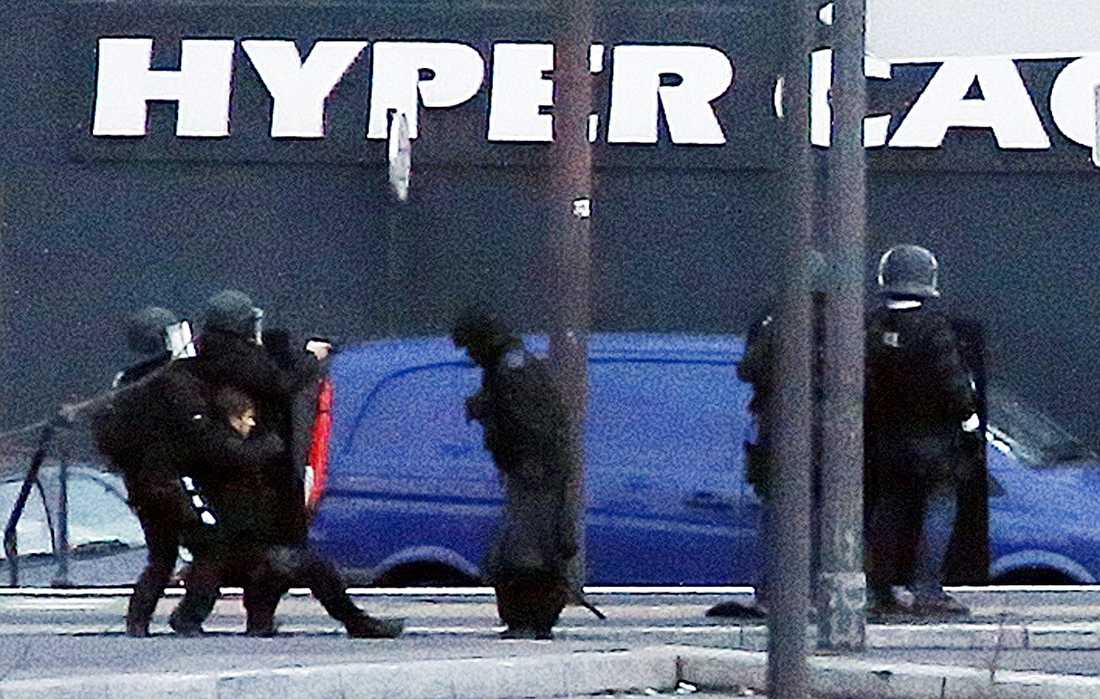 En skadad polis får hjälp av sina kollegor under stormningen av butiken där gisslan hölls i Paris.