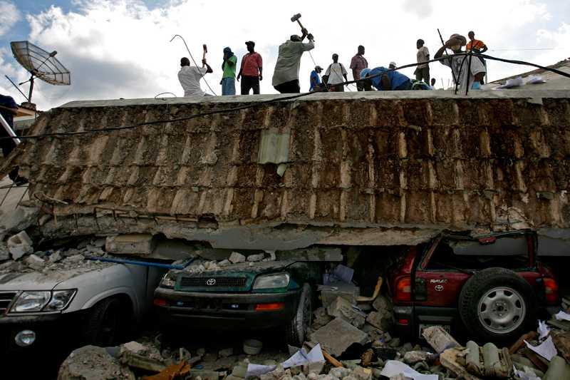 Människor tar vad de har för att gräva fram överlevande ur rasmassorna i Port-au-Prance.