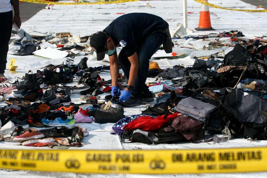 En utredare går igenom saker som hittats efter kraschen i Indonesien. Arkivbild.