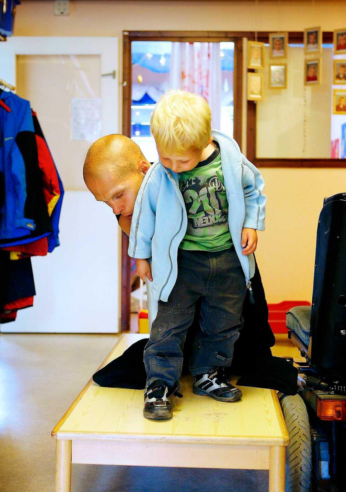 """Påklädning. """"Jag hjälper Linus ta av och på kläderna. Han reder sig själv med mina instruktioner"""", säger Mikael."""