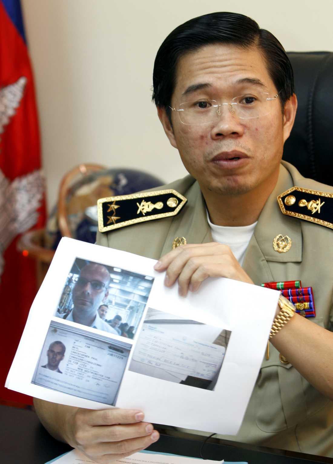 REDO ATT GRIPA HONOM. Chefen för Interpols kontor i Kambodja håller upp bilder och passuppgifter gällande Christopher Paul Neil, den så kallade virvelpedofilen. Kambodja gränsar till Thailand, där Neil reste in förra veckan.