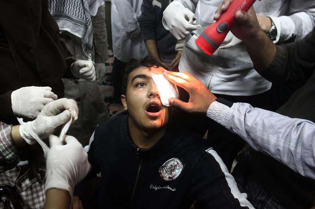 En demonstrant får läkarvård i ett provisoriskt sjukläger vid Tahrir-torget i Kairo. Mannen har skjutits i ögat.