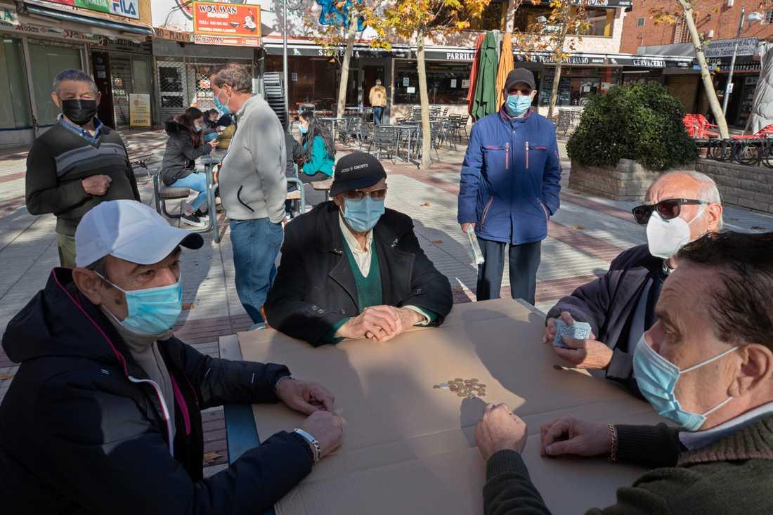 Pensionärer spelar kort på ett torg i den spanska huvudstaden Madrid, som i likhet med den lilla staden Tomelloso drabbats hårt av coronaviruset.