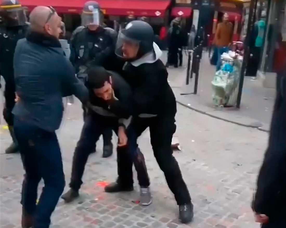 Mannen till höger har identifierats som säkerhetsvakt hos Frankrikes president Emmanuel Macron. Från en upptagning som gjordes i Paris på första maj.