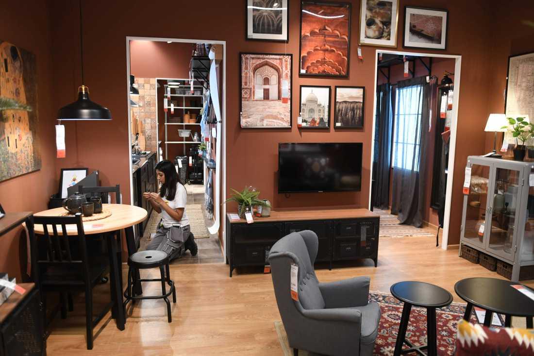 En Ikea-anställd gör i ordning ett av butikens visnings-vardagsrum.