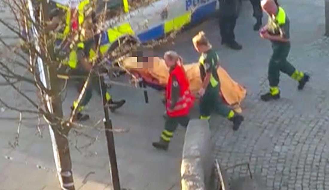 Den skjutne förs bort av ambulans.