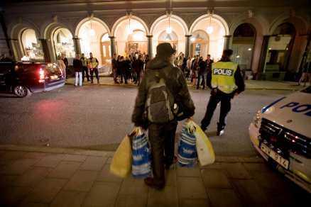 inte välkommen Uteliggaren Hannu, 51, står utanför festen. Han är också en del av Fredrik Reinfeldts nya Sverige. Men polisen bevakar honom noggrant.