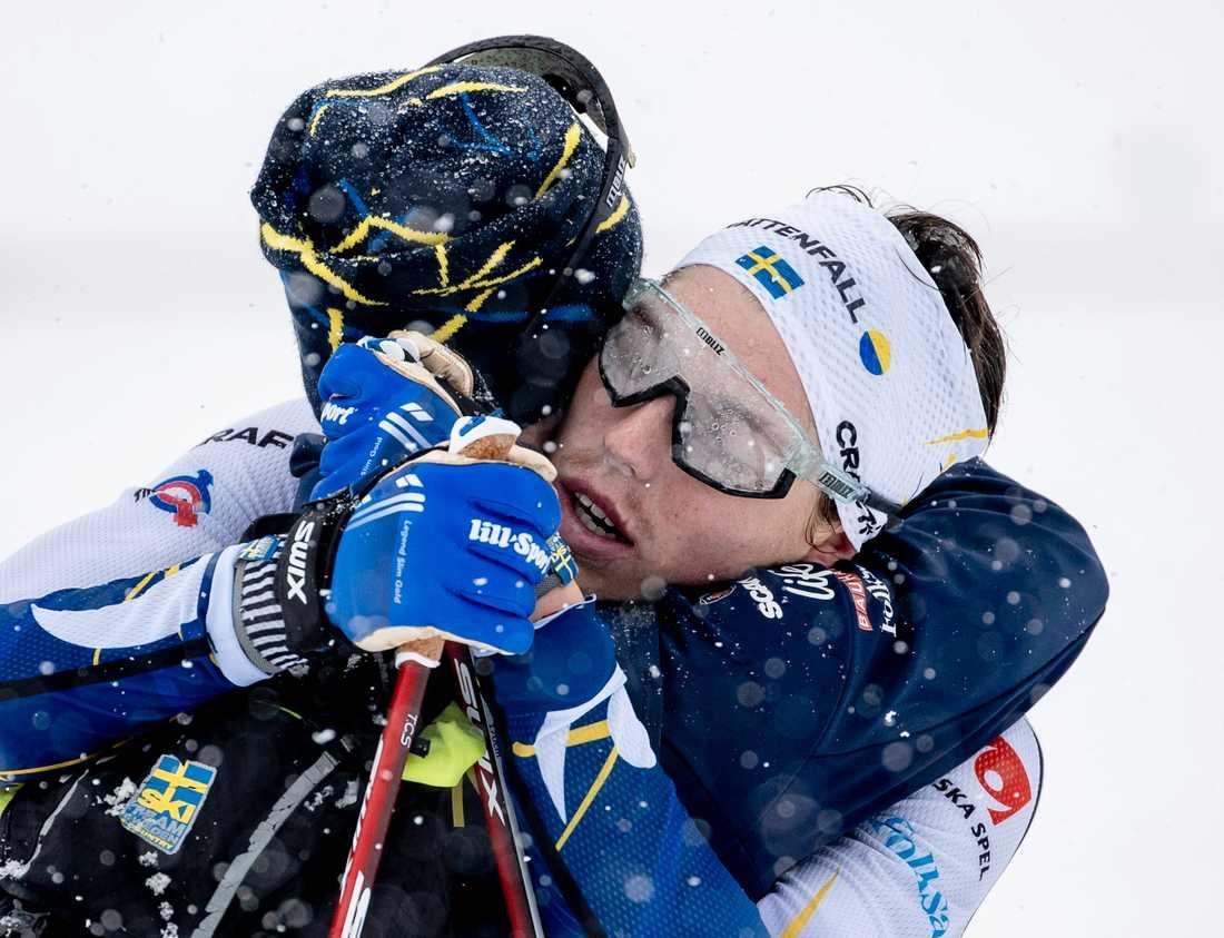 Jens Burman kramar om William Poromaa efter målgången på herrarnas stafett under skid-VM i Oberstdorf.