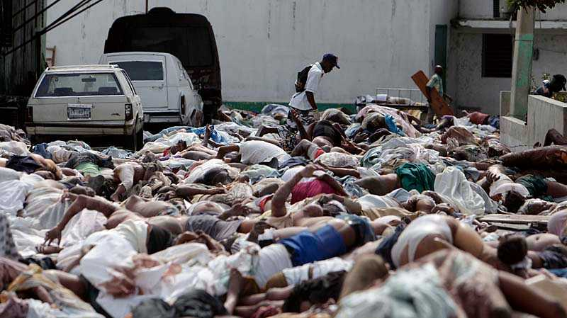 En man letar efter anhöriga bland alla kroppar som nu ligger helt öppet på gatorna i Port-au-Prince.