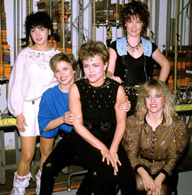 Axelvaddar och orange läppstift Belinda Carlisle med sitt band The Go-Go's 1983.