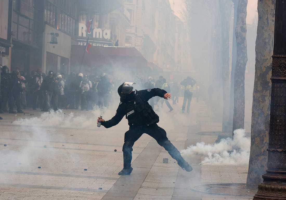 En polis kastar tårgas.