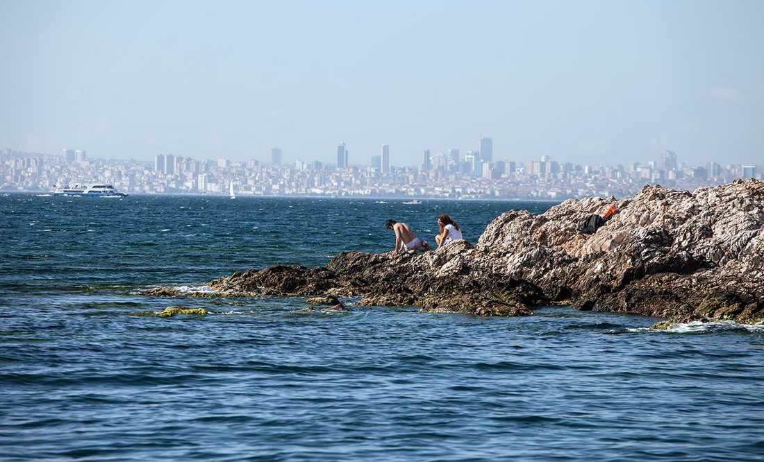 Liten strand på ön Heybeliada med Istanbuls husgytter i bakgrunden.
