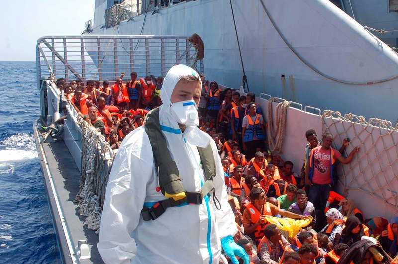 Det här fotot, från augusti förra året, visar flyktingar som väntar på att få kliva ombord på kustbevakningens fartyg utanför Lampedusa.