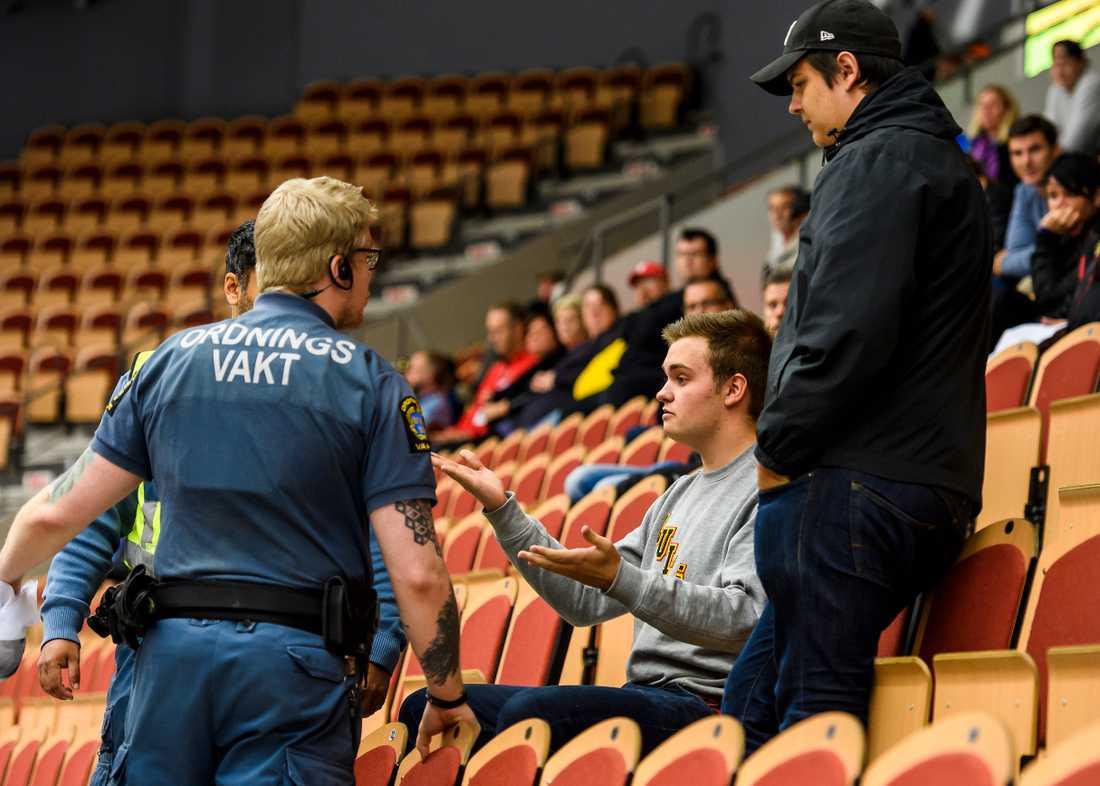 """Vakter stoppar två supportrar från att hänga upp en """"avgå Boork"""" banderoll bakom Sveriges avbytarbänk."""