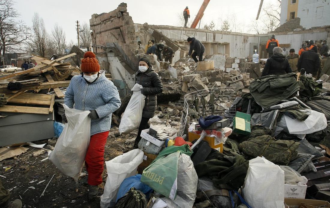 Människor samlar ihop sina tillhörigheter i ruinerna av en byggnad i Donetsk som träffades av granatbeskjutning i februari i år, då både regerings- och rebellkontrollerade områden utsattes för beskjutning.