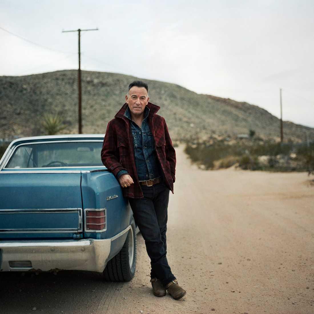 Bruce Springsteen lutar sig mot en bil.
