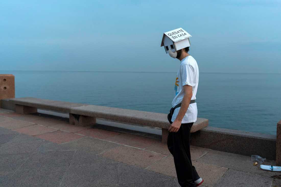 """En man med munskydd och pappkartongshus som huvudbonad, med texten """"stanna hemma"""", promenerar längs Montevideos strandpromenad."""