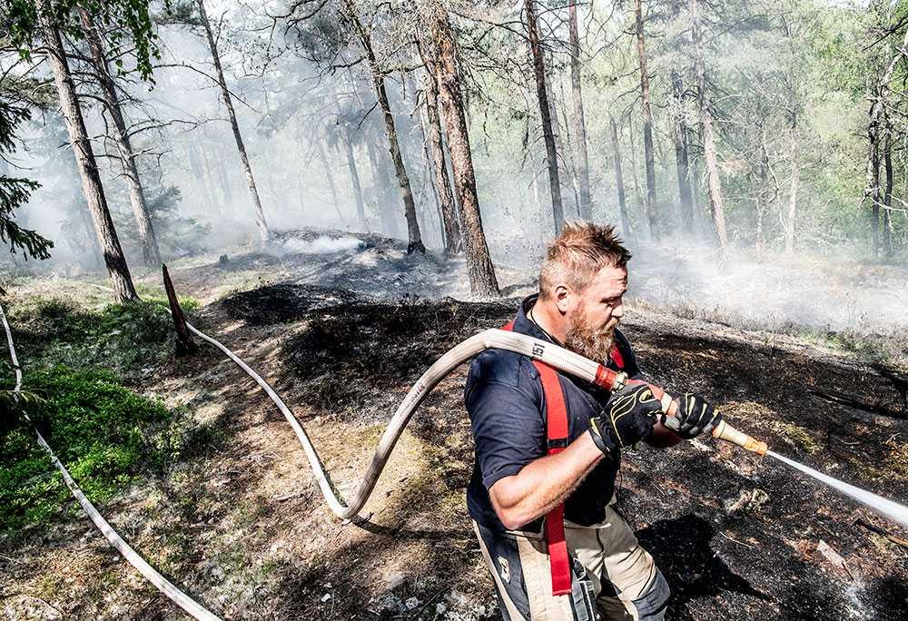 En brandman släcker en markbrand i Stortorp i maj 2019.