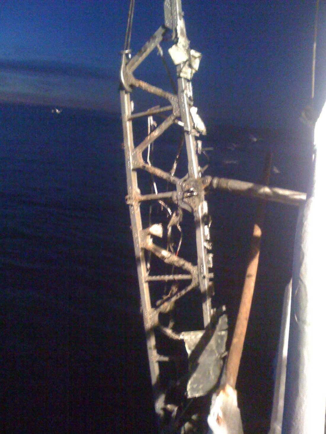 Bilden visar vingen som hänger i en kran på sidan av fartyget efter att besättningen fått loss den från trålen. –Det man ser är den fem meter långa balken som sticker ut ur vingen där vingen brutits loss. Efter balken fortsätter vingen ca 10-12 meter ned i vattnet där själva vingprofilen är, som inte syns i bild, säger en fiskare på båten.