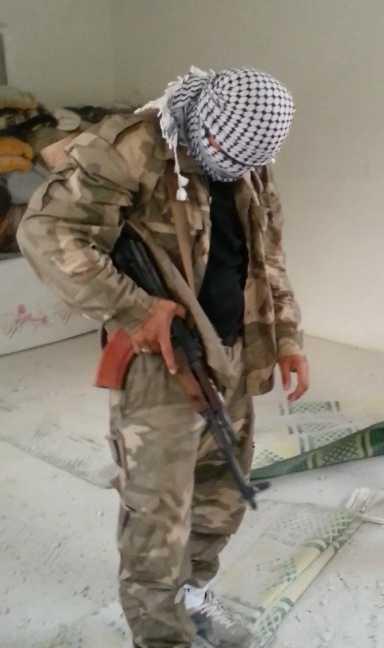 En ung svensk jihadist kontrollerar sitt vapen i ett sönderbombat hus utanför Aleppo.